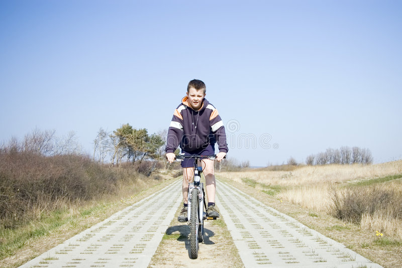 Menino que monta uma bicicleta. fotografia de stock