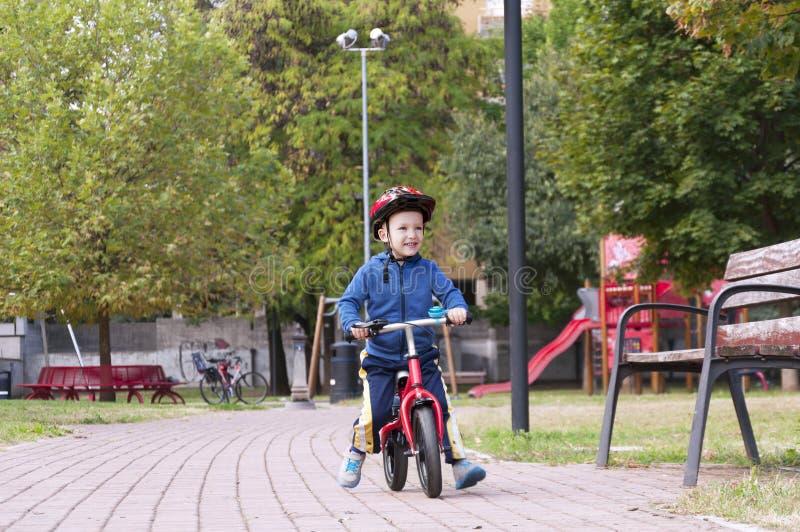 Menino que monta uma bicicleta no parque fotos de stock royalty free