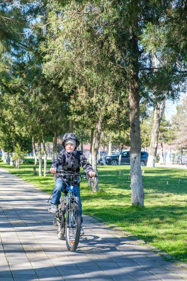 Menino que monta uma bicicleta no parque imagens de stock