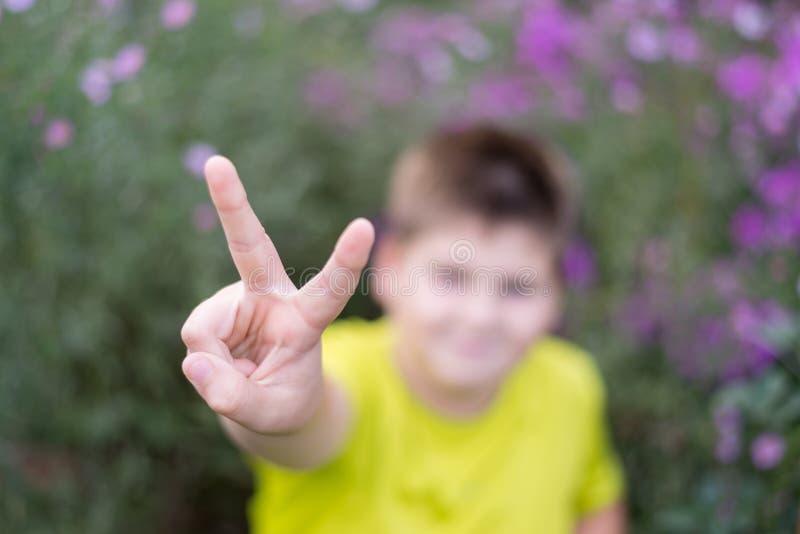 Menino que mostra o gesto do sinal da vitória imagens de stock royalty free