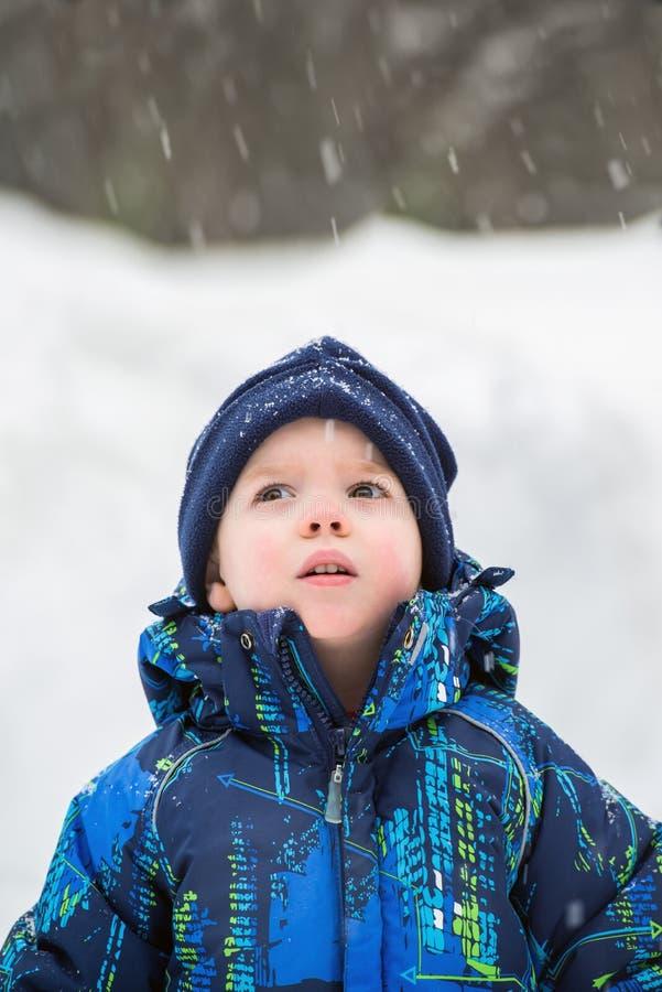 Menino que olha acima na maravilha na queda da neve foto de stock royalty free