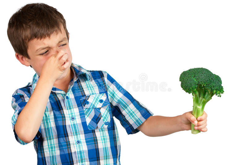 Menino que olha brócolis com aversão imagem de stock