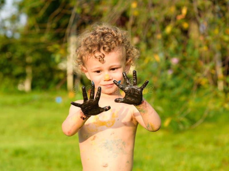 Menino que olha cepticamente em suas palmas pretas pintadas com pintura de óleo imagens de stock