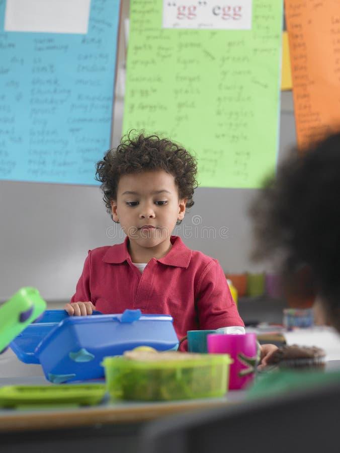 Menino que olha na cesta de comida na classe foto de stock royalty free