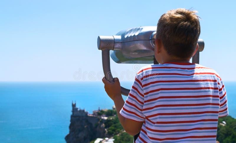 Menino que olha nos binóculos em um castelo da observação imagens de stock