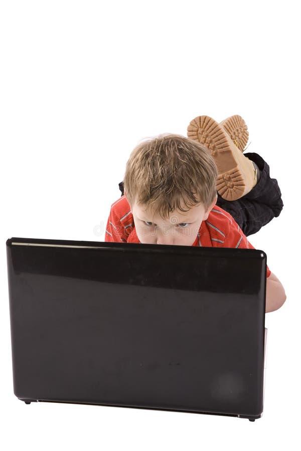 Menino que olha o computador imagem de stock