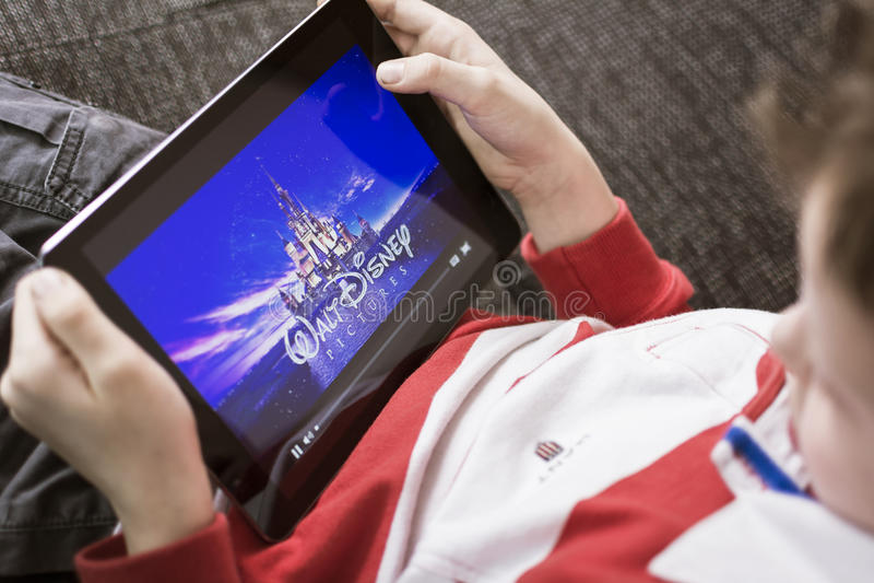Menino que olha o filme de Disney no PC da tabuleta foto de stock royalty free