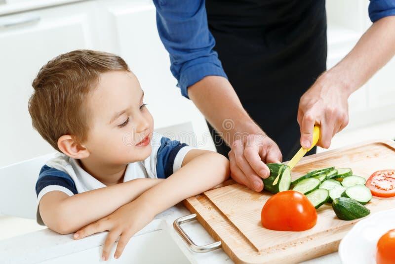 Menino que olha o pai ao cozinhar imagem de stock