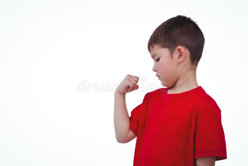 Menino que olha seu bíceps fotografia de stock