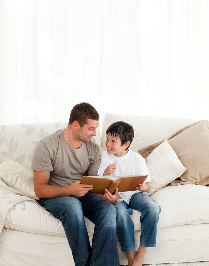 Menino que olha um álbum de foto com seu pai fotos de stock royalty free