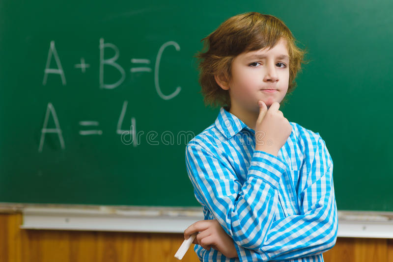 Menino que pensa no fundo do quadro-negro Conceito educacional e da escola imagens de stock royalty free