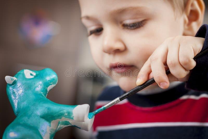 Menino que pinta a figura cerâmica imagens de stock royalty free