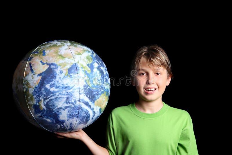 Menino que prende a esfera da terra do mundo em sua mão fotos de stock