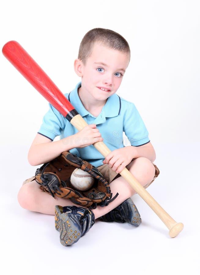 Menino que prende um bastão de beisebol com esfera e luva foto de stock royalty free