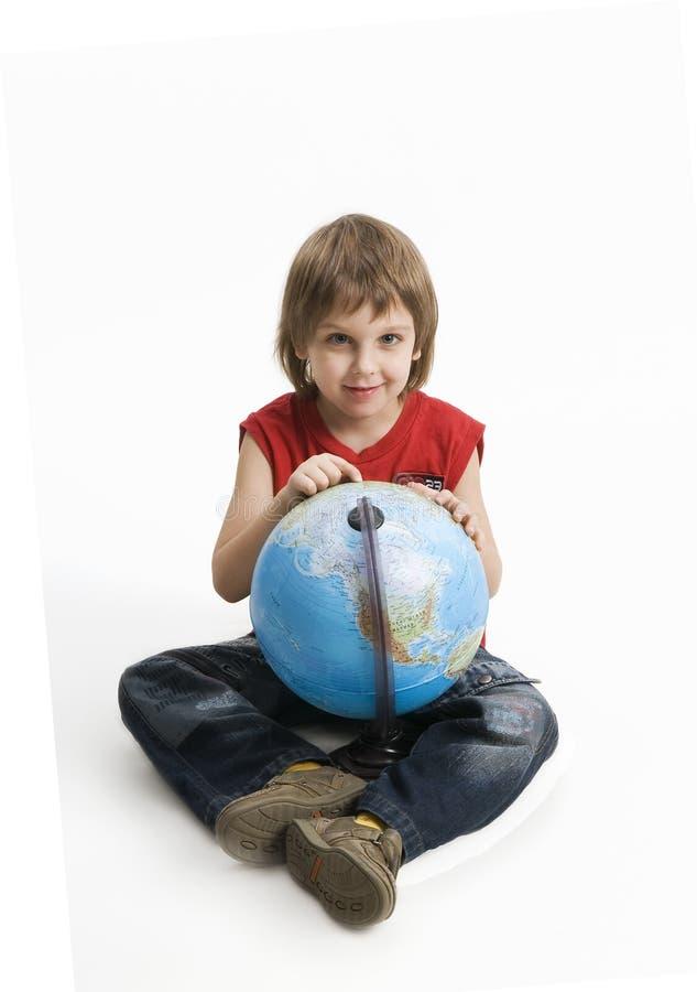 Menino que prende um globo em suas mãos em um branco fotografia de stock royalty free