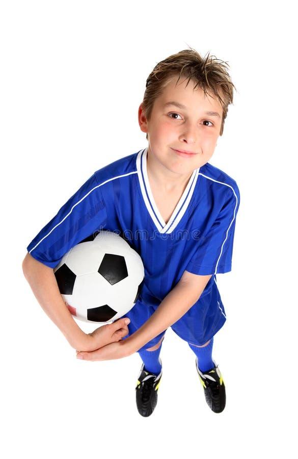 Menino que prende uma esfera de futebol fotografia de stock