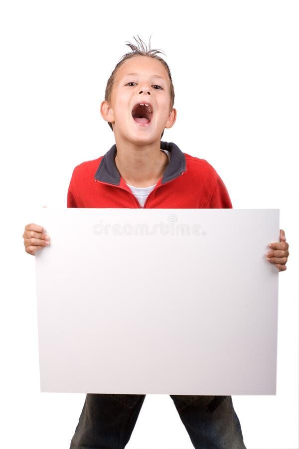 Menino que prende uma placa branca do sinal foto de stock royalty free