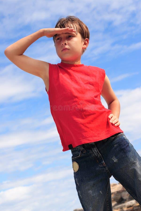 Menino que procurara olhando a mão à testa fotografia de stock