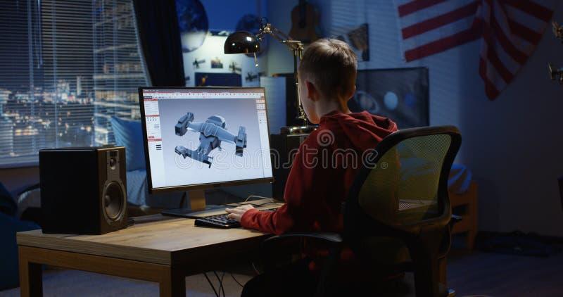 Menino que projeta o avião em um computador fotografia de stock royalty free