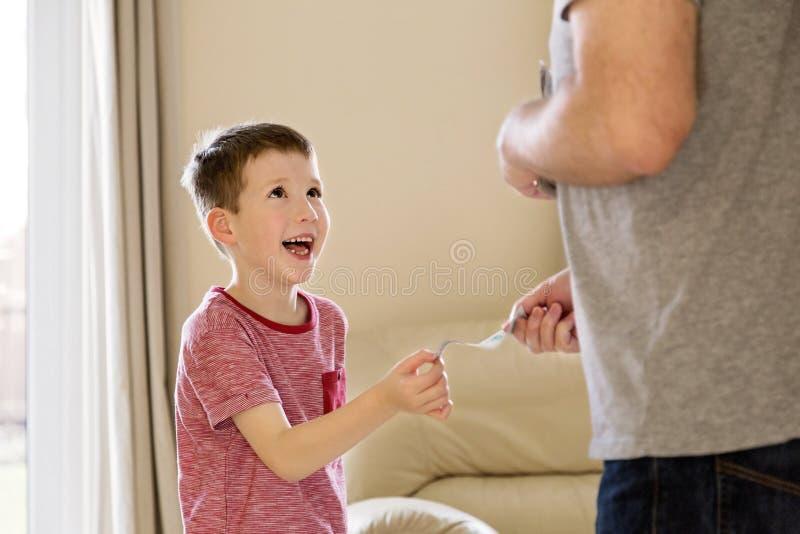 Menino que recebe o dinheiro de bolso (permissão) do pai fotos de stock royalty free