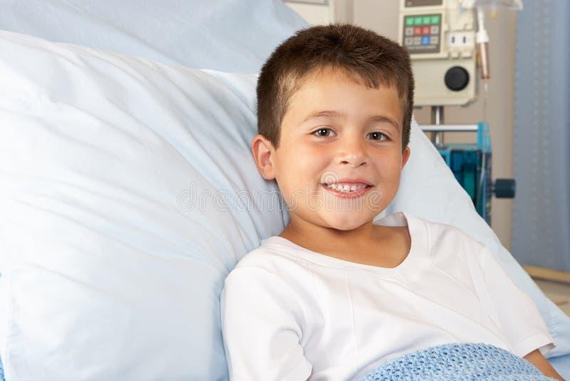 Menino que relaxa na cama de hospital foto de stock
