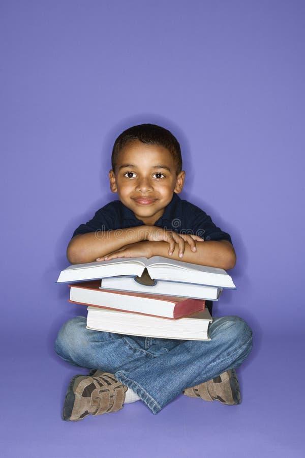 Menino que senta-se com livros. imagens de stock