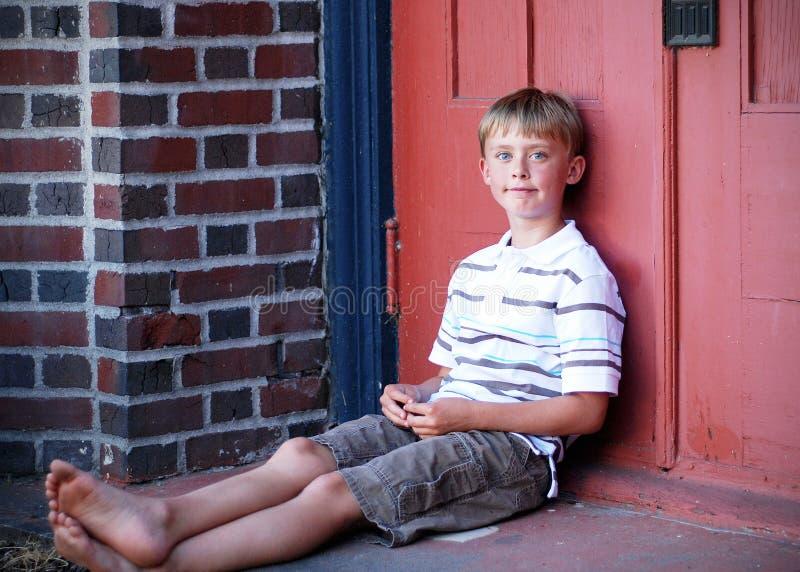 Menino que senta-se de encontro à parede vermelha - horizontal fotografia de stock