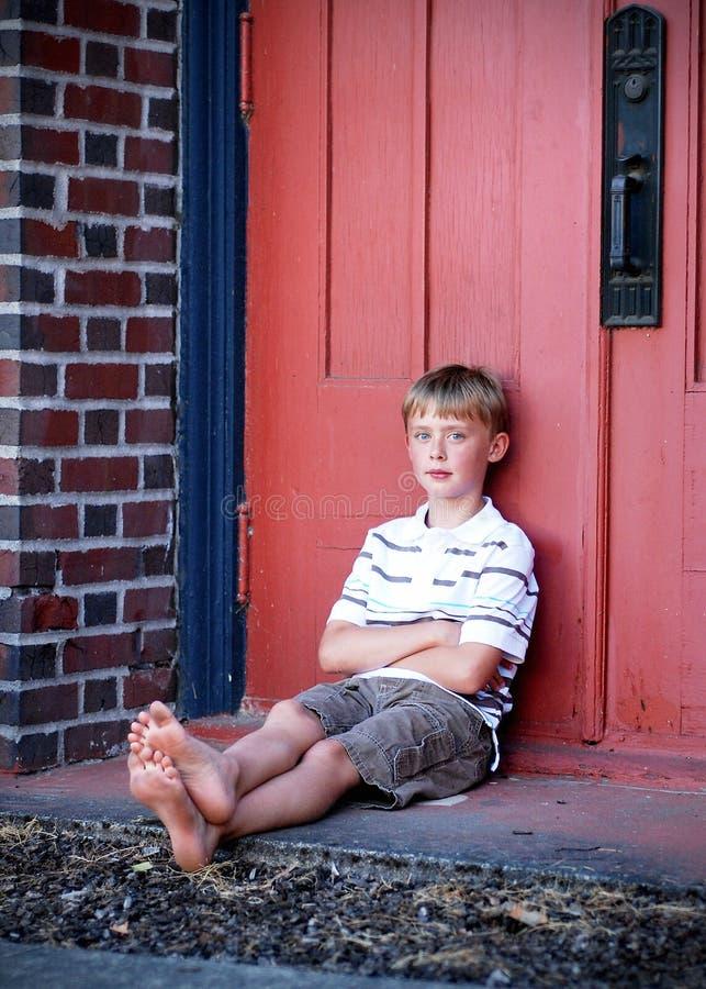 Menino que senta-se de encontro à parede vermelha - vertical fotografia de stock