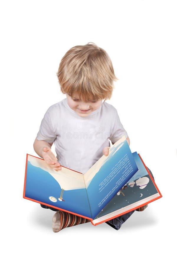 Menino que senta-se lendo um livro de retrato grande foto de stock royalty free