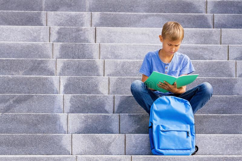 Menino que senta-se nas escadas e que faz trabalhos de casa da escola foto de stock royalty free
