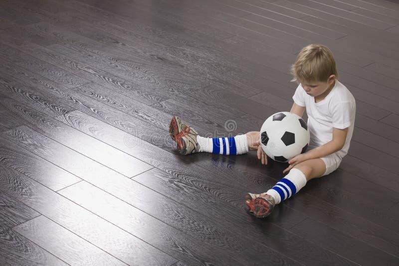 Menino que senta-se no assoalho com bola de futebol fotografia de stock