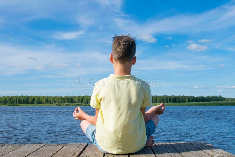 Menino que senta-se no cais, em uma pose da ioga, fora imagem de stock royalty free