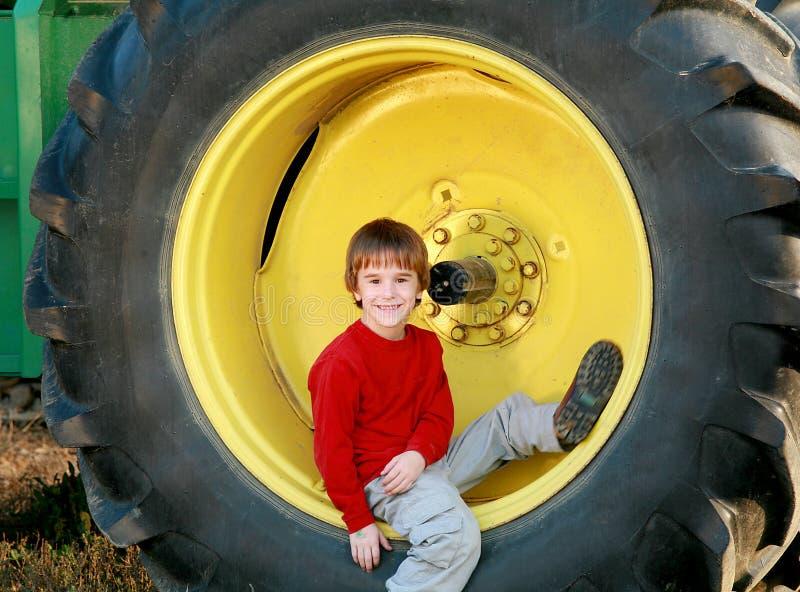 Menino que senta-se no pneu   fotografia de stock