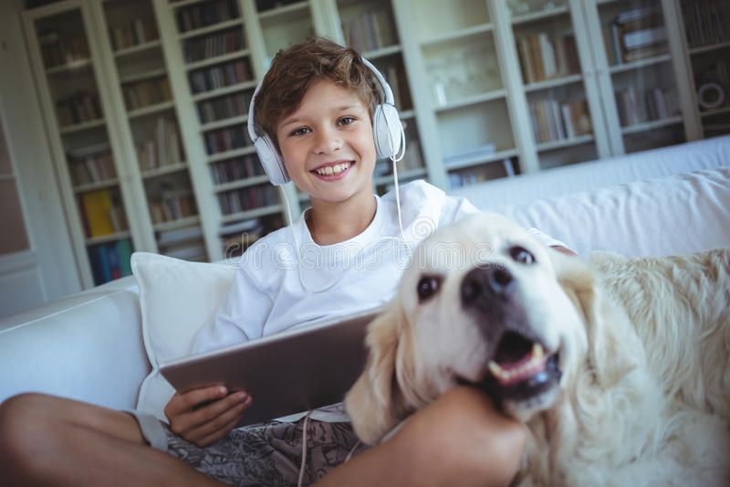 Menino que senta-se no sofá com cão de estimação e que escuta a música na tabuleta digital fotos de stock royalty free