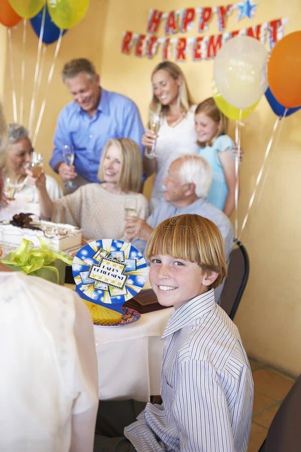 Menino que sorri com a família que tem um partido de aposentadoria imagem de stock royalty free