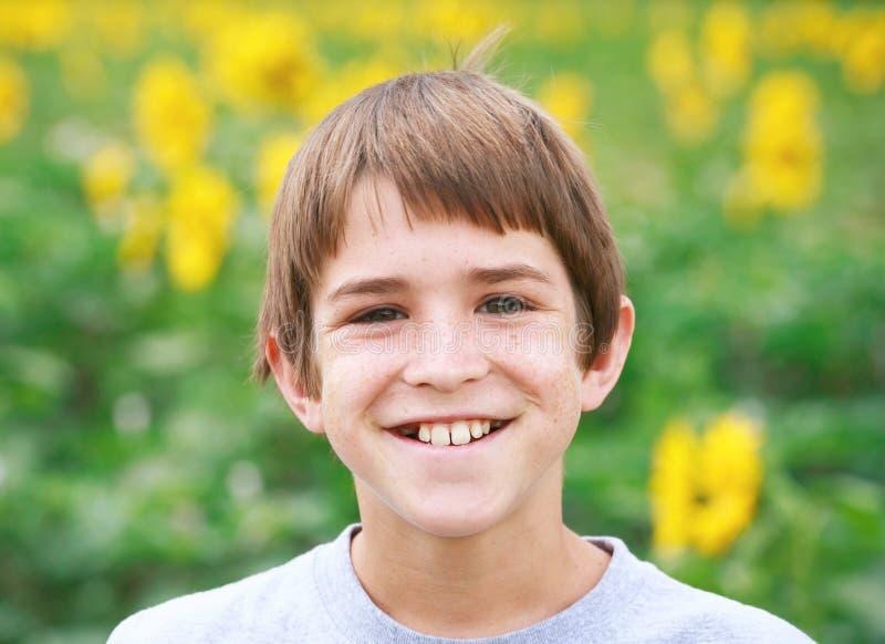 Menino que sorri em um campo de flor foto de stock