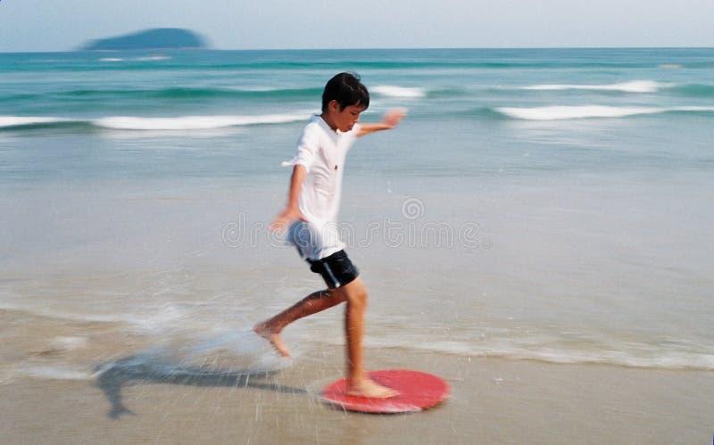 Menino que surfa através das ondas imagem de stock royalty free