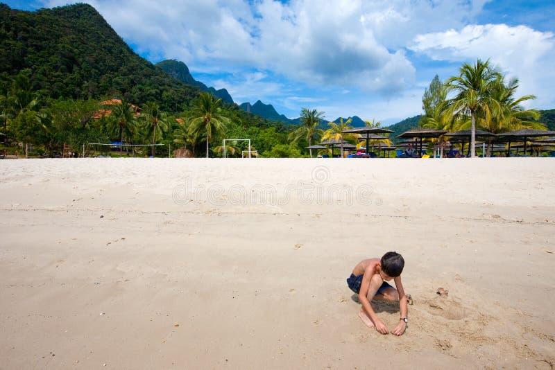 Menino que tem o divertimento que joga fora na areia pela praia na ilha tropical fotos de stock royalty free