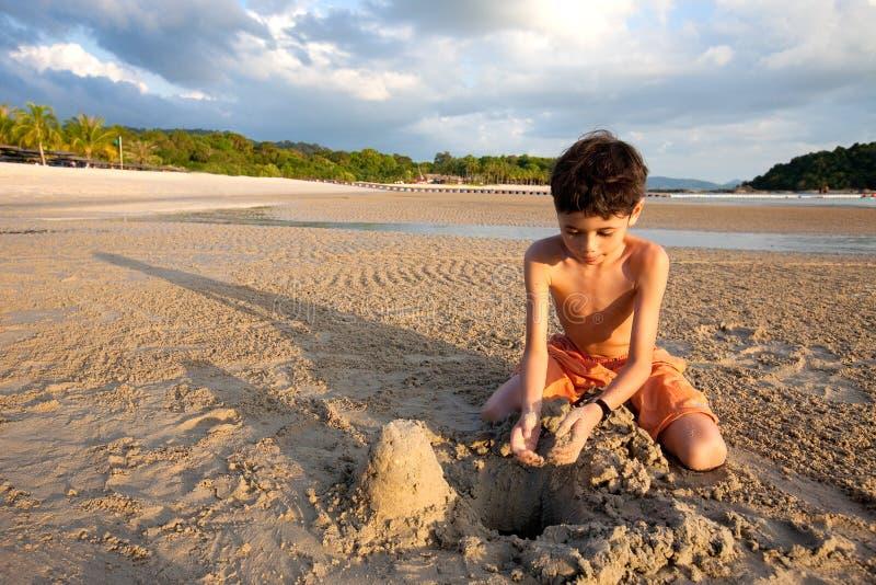 Menino que tem o divertimento que joga fora na areia pela praia no por do sol fotos de stock royalty free