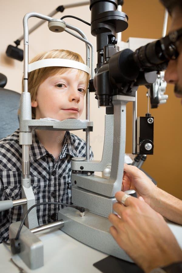 Menino que tem seu olho testado com a lâmpada cortada pelo doutor fotos de stock