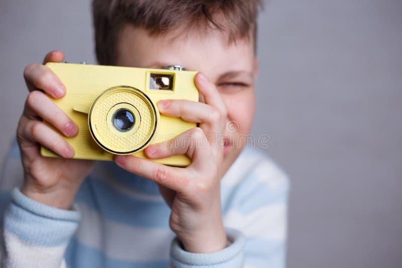 Menino que toma uma imagem com câmera do vintage Fotografia, passatempo e fotos de stock royalty free
