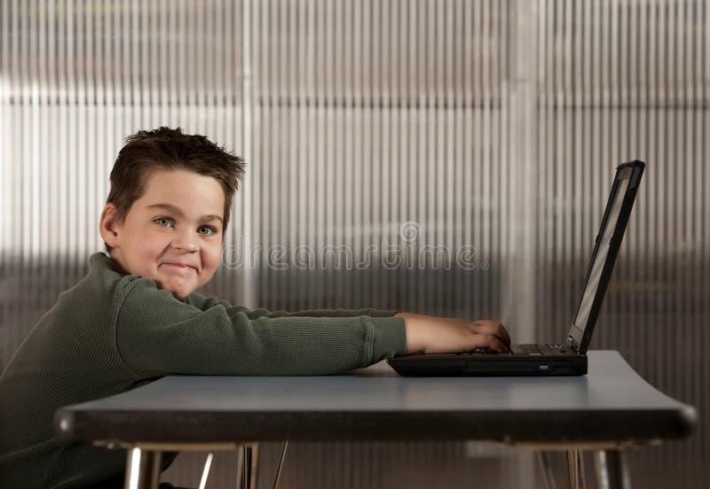Menino que trabalha em um computador portátil foto de stock