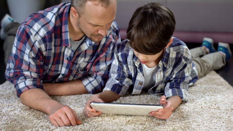 Menino que usa a aplicação interativa na tabuleta com ajuda do pai, tempo da família fotografia de stock