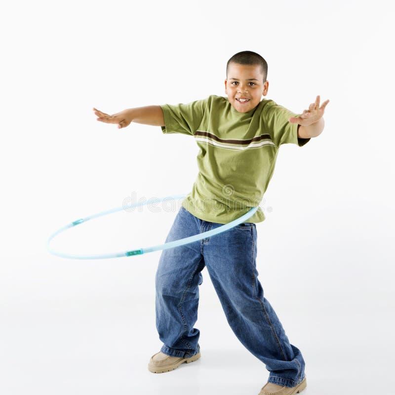 Menino que usa a aro do hula. fotografia de stock royalty free