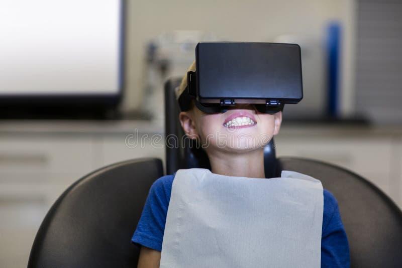 Menino que usa auriculares da realidade virtual durante uma visita dental fotografia de stock royalty free
