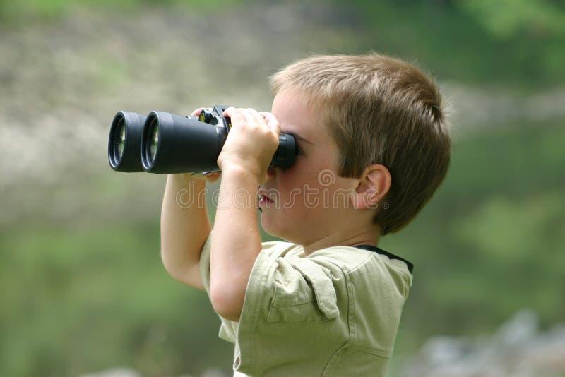 Menino que usa binóculos imagens de stock