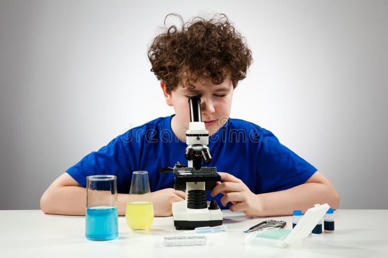 Menino que usa o microscópio foto de stock