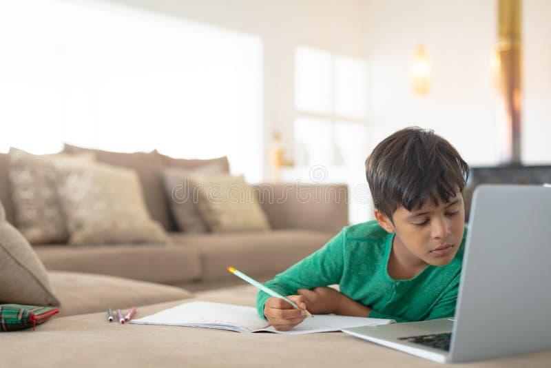 Menino que usa o portátil ao tirar um esboço no livro em casa foto de stock royalty free