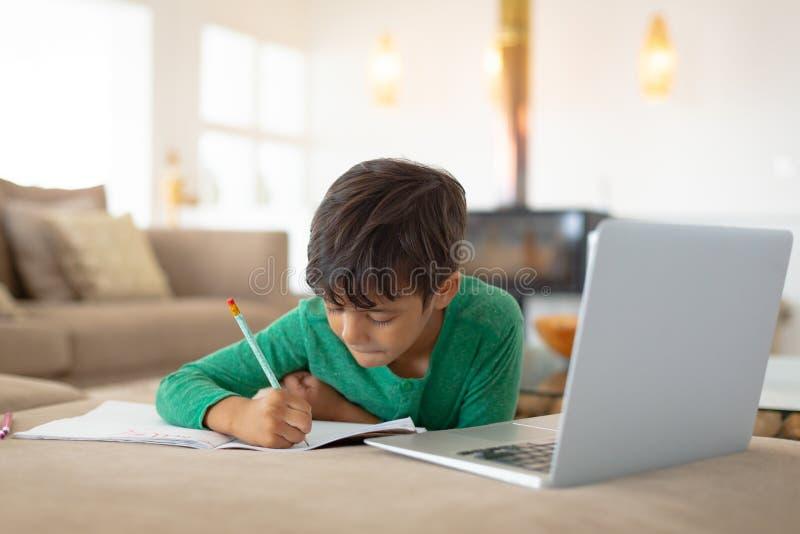 Menino que usa o portátil ao tirar um esboço no livro em casa fotos de stock royalty free