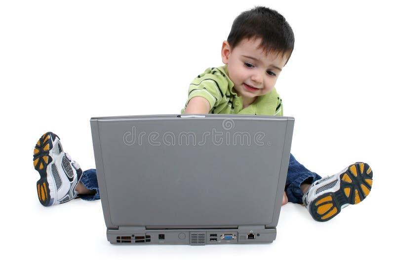 Menino que usa o portátil com trajeto de grampeamento imagem de stock